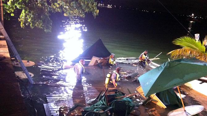 In this photo provided by WSVN-TV, divers search the water after a deck collapse at Shuckers Bar & Grill in Miami Thursday night, June 13, 2013. The deck collapsed during the NBA Finals on Thursday night, sending dozens of patrons into the shallow waters of Biscayne Bay. Three people were critically injured. (AP Photo/WSVN-TV, Tom Tuckwell) MANDATORY CREDIT