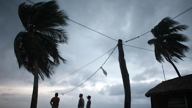 People look out at the beach as Tropical Storm Isaac approaches in Barahona, Dominican Republic, Friday, Aug. 24, 2012.   Isaac strengthened slightly as it spun toward the Dominican Republic and Haiti, but seemed unlikely to gain enough steam early Friday to strike the island of Hispaniola as a hurricane. The storm's failure to gain the kind of strength in the Caribbean that forecasters initially projected made it more likely that Isaac won't become a hurricane until it enters the Gulf of Mexico, said Eric Blake, a forecaster with U.S. National Hurricane Center in Miami. (AP Photo/Ricardo Arduengo)