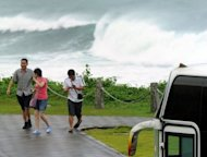 Chinese tourists walk near the coast of Hualien, eastern Taiwan, on August 23, 2012. Typhoon Tembin made landfall in Taiwan early Friday, toppling trees and ripping off rooftops in exposed areas in the south of the island, officials said