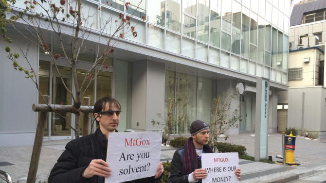 Bitcoin trader Kolin Burges, right, of London and American Aaron (only his first name was given) hold protest signs as they conduct a sit-in in front of the office tower housing Mt. Gox in Tokyo Tuesday, Feb. 25, 2014. The website of major Bitcoin exchange Mt. Gox is offline Tuesday amid reports it suffered a debilitating theft, a new setback for efforts to gain legitimacy for the virtual currency. The URL of Tokyo-based Mt. Gox was returning a blank page. The disappearance of the site follows the resignation Sunday of Mt. Gox CEO Mark Karpeles from the board of the Bitcoin Foundation, a group seeking legitimacy for the currency. Burgess said he had picketed the building since Feb. 14 after flying in from London, hoping to get back $320,000 he has tied up with Mt Gox. (AP Photo/Kaori Hitomi)