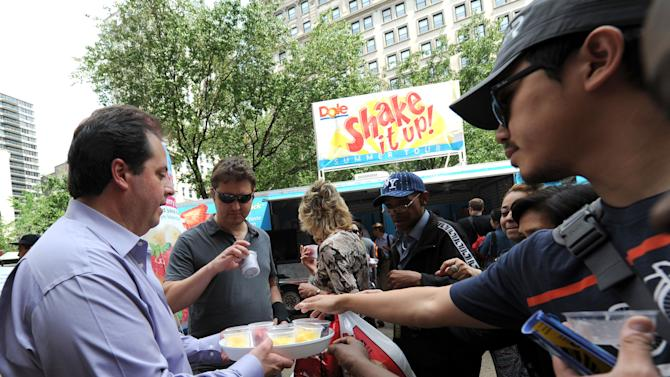 Crowds enjoy free samples of DOLE Frozen Fruit Single-serve Cups at the DOLE Shake It Up!  Summer Tour in New York's Herald Square, Wednesday, May 16, 2012.  The event also gave out samples of DOLE Fruit Smoothie Shakers.  (Diane Bondareff/AP Images for DOLE)