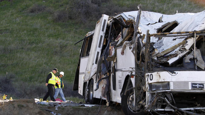 Authorities continue their investigation of the scene where at least eight people were killed and at least 38 people were injured after a tour bus carrying a group from Tijuana, Mexico crashed with two other vehicles just north of Yucaipa, Calif., Sunday, Feb. 3, 2013. (AP Photo/Reed Saxon)