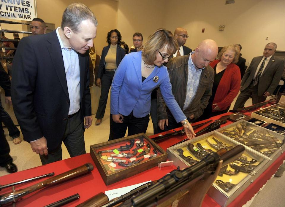 New York Attorney General Eric Schneiderman, left, former Arizona congresswoman Gabrielle Giffords, center, and her husband Mark Kelly tour the New EastCoast Arms Collectors Associates arms fair in Saratoga Springs, N.Y. on Sunday, Oct. 13, 2013. (AP Photo/Tim Roske, Pool)