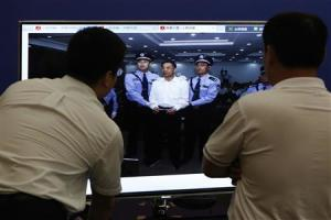 Men look at a picture of disgraced Chinese politician Bo standing trial on the website of a court's microblog, in Jinan