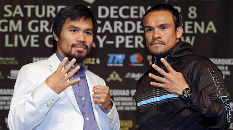 Manny Pacquiao, left, and Juan Manuel Marquez, right, pose for photos during a news conference, Wednesday, Dec. 5, 2012, in Las Vegas. Pacquiao and Marquez are scheduled to face off in a welterweight boxing match on Saturday. (AP Photo/Julie Jacobson)