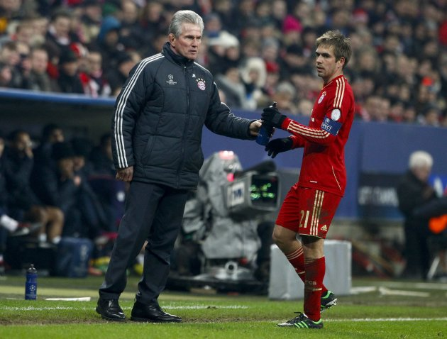 Bayern Munich coach Heynckes hands over a bottle to Lahm during their Champions League round of 16 second leg soccer match against Arsenal in Munich