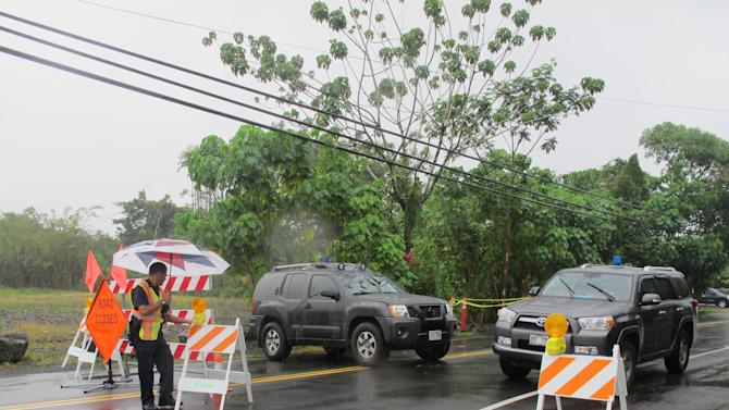 Police block traffic on Wednesday, Oct. 29, 2014 where officials expect lava to flow across the main road in Pahoa, Hawaii. Rain fell on a red-hot river of lava as it threatened to consume its first home on its slow advance into a rural Hawaii town. (AP Photo/Audrey McAvoy)