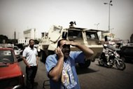 An Egyptian man talks on the telephone in front of an army vehicle in central Cairo&#39;s Tahrir Square in May 2012. For people living in countries where the the government monitors and censors the Internet, help is on the way