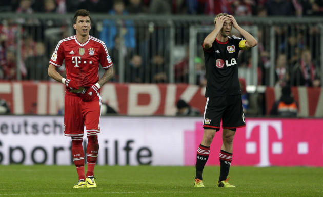 Bayern's Mario Mandzukic of Croatia, left, watches the stadium board after scoring his side's opening goal as Leverkusen's Simon Rolfes gestures during the German first division Bundesliga