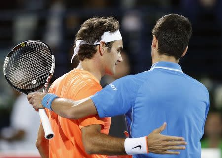 Roger Federer shakes hand with Novak Djokovic after their final match at the ATP Championships tennis tournament in Dubai