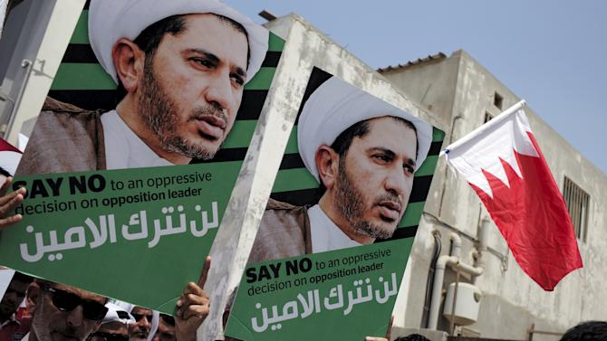 Protesters hold placards with photos of opposition leader and head of Al Wefaq party Ali Salman during a protest after Friday prayers in the village of Diraz west of Manama