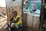 A woman points to election posters for President John Mahama at Bosomtwe Sam fishing harbour, Sekondi on Saturday. Mahama says the idea of free secondary education in Ghana is great on paper, but not yet possible as the money shortage could greatly harm education in this nation of 20 million people