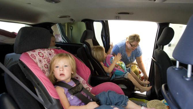 Lisel Christiansen packs her van with her children Ellie, 4,  Luci, 2, front, and Madelyn, 9,  and items as she prepares to leave her home in Eagle Mountain, Utah Friday, June 22, 2012.  Officials say about 250 homes are being evacuated after high winds kicked up a fire near a northern Utah dump. Fire officials say the blaze just west of the Saratoga Springs landfill has burned more than 750 acres. (AP Photo/The Salt Lake Tribune, Paul Fraughton)