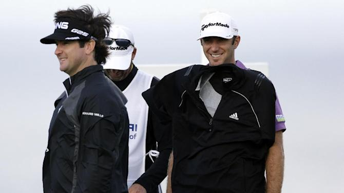 Dustin Johnson, right, demonstrates how strong the wind is by letting it hold his jacket against him as he stands with Bubba Watson on the14th hole during the first round at the Tournament of Champions PGA golf tournament Monday, Jan. 7, 2013 in Kapalua, Hawaii. Play was to have started three days earlier, but was delayed because of rain and high winds. (AP Photo/Elaine Thompson)