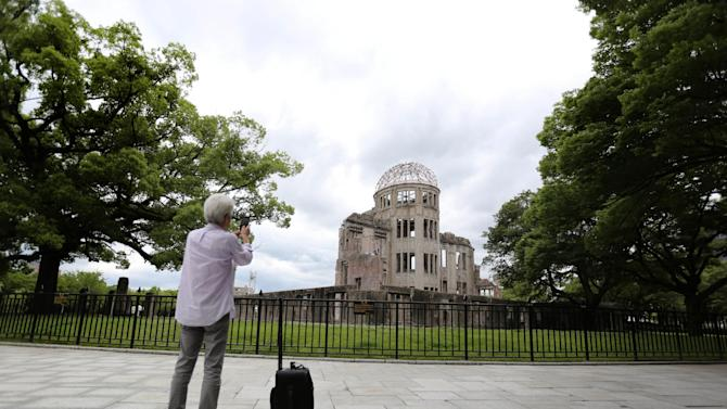 In this July 1, 2015 photo, a visitor photographs now known as Atomic Bomb Dome in Hiroshima, western Japan. On Aug. 6, 1945, a U.S. plane dropped an atomic bomb on Hiroshima, the first nuclear weapon has been used in war. Japan surrendered on Aug. 15, ending World War II. (AP Photo/Eugene Hoshiko)