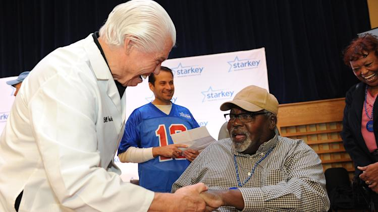 Bill Austin, founder of Starkey Hearing Foundation, fits musician Smokey Johnson with a new hearing aid as his wife Gwen Johnson watches on Saturday, Feb. 2, 2013 in New Orleans. (Photo by Cheryl Gerber/Invision for Starkey Hearing Foundation/AP Images)