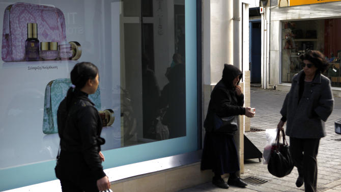 "A female panhandler stands on a corner of a busy shopping street in the old part of Cyprus'  capital Nicosia, on Wednesday, Jan. 23, 2013.  Cyprus says that international allegations it is a haven for money laundering amount to a ""war"" and must stop. Cyprus is trying to finalize an agreement with the European Commission, the European Central Bank and the IMF on a bailout to help rescue its banks, which lost billions on bad Greek debt. (AP Photo/Petros Karadjias)"