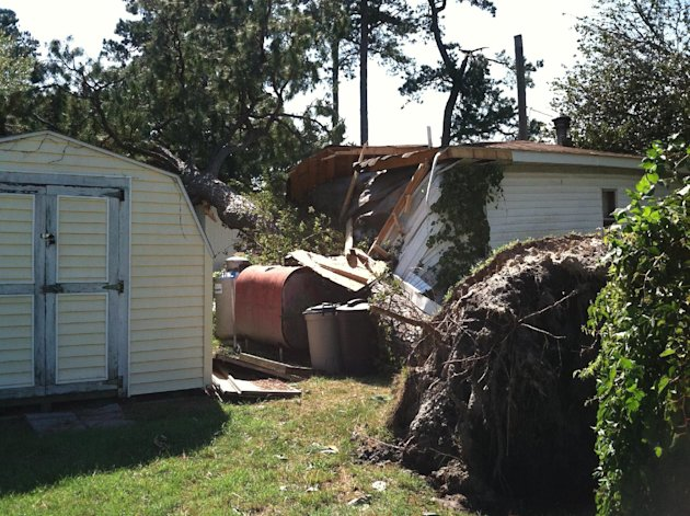 A mobile home sits damaged from two trees that fell on it in Chincoteague, Va., Sunday, Aug. 28, 2011. However, it was unclear if the cause was Hurricane Irene or a possible tornado. The family that l