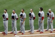 St. Louis Cardinals players stand during the singing of the national anthem before the Opening Day baseball game against the Miami Marlins, Wednesday, April 4, 2012, in Miami. (AP Photo/Wilfredo Lee)