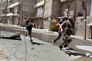 "Rebel fighters run for cover during fighting in the al-Mashad neighbourhood of the northern city of Aleppo on August 25. Dozens of bodies were found as Syrian forces launched a deadly assault in the southwestern belt of Damascus on Saturday, in what activists said was a new bid to crush ""once and for all"" the insurgency in the capital"