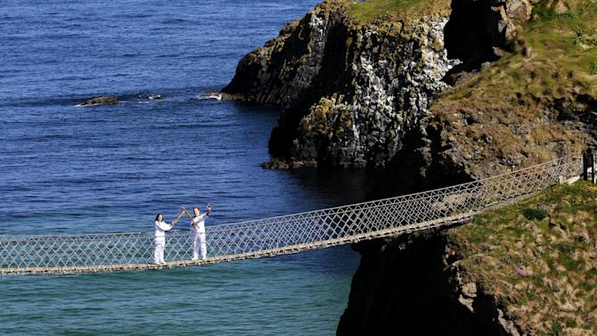 Clare Leahy, left, lights Denis Broderick during a change over of the  the Olympic Torch at the Carrick-a-Rede rope bridge in county Antrim, Northern Ireland, Monday, June 4, 2012. The Olympic Torch is continuing its relay journey around the country, and is scheduled to arrive at the opening ceremony of the London 2012 Olympic Games.  (AP Photo/Peter Morrison)