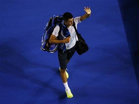 Bernard Tomic of Australia leaves the court after being defeated by Roger Federer of Switzerland in their men's singles match at the Australian Open tennis tournament in Melbourne