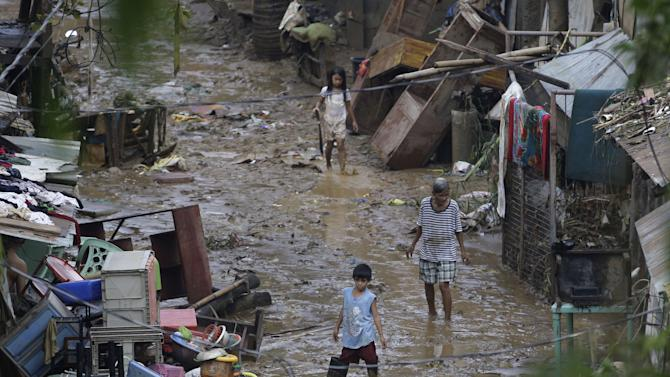 Residents stand on mud outside their homes after floods recede in suburban Marikina city, east of Manila, Philippines, Friday Aug. 10, 2012. Philippine disaster officials were shifting Friday from rescue work to a massive clean-up of the capital following nonstop rains that left tons of muck and debris from floods littering the city. (AP Photo/Aaron Favila)