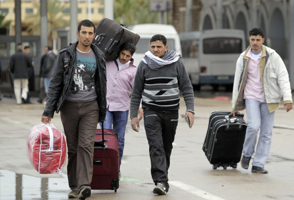 Tunisian men who fled from Libya carry their belongings at the Tunisia-Libyan border, bear the town of Ben Guerdane,Tunisia, Wednesday, Feb. 23, 2011. (AP Photo/Lefteris Pitarakis)