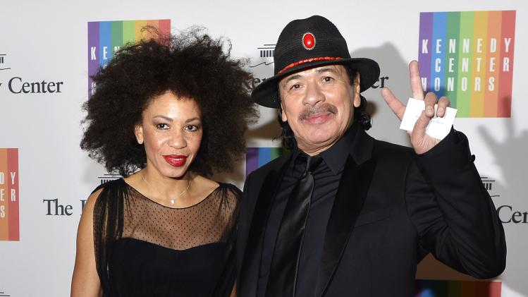 Carlos Santana gestures as he and his wife arrive at the U.S. State Department for a gala dinner in Washington