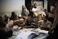 Egyptian election officials count ballots at a polling station in a Cairo school. Vote counting was underway in Egypt after two days of polling ended Thursday in a landmark presidential election which pitted stability against the ideals of the uprising that ended Hosni Mubarak&#39;s rule