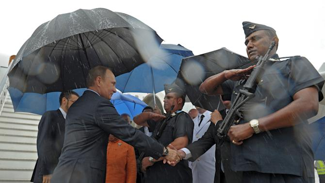 Russian President Vladimir Putin, left, is welcomed on his arrival in Durban, South Africa, Tuesday, March 26, 2013. Vladimir Putin is on a working visit and set to meet with South African officials on Tuesday before attending a meeting with the leaders of Brazil, Russia, India and China (BRICS) during an Africa Dialogue Forum in Durban on Wednesday. (AP Photo/RIA-Novosti, Alexei Druzhinin, Presidential Press Service,Pool)