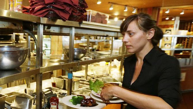 In this June 2, 2014 photo, Wendy Harrison, a waitress at the icon Grill in Seattle, picks up a food order from the kitchen as she works during lunchtime. An Associated Press comparison of the cost of living at several other major U.S. cities found that a $15 minimum wage, like Seattle adopted this week, will make a difference, but won't buy a lavish lifestyle. (AP Photo/Ted S. Warren)