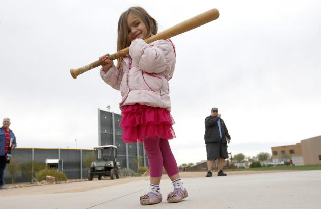 Arizona Diamondbacks fan Sophia Piermarini, 3, walks around with her baseball bat after getting an autograph from Diamondbacks' Paul Goldschmidt, as players report to the Diamondbacks spring train