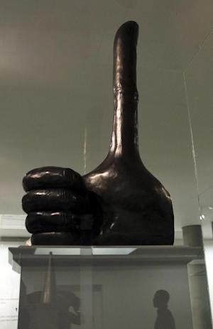 """British artist David Shrigley's 32-foot (10-meter) bronze thumb sculpture which is one of six proposals for the fourth plinth in Trafalgar Square, central London, exhibited in St Martin-in-the-Fields Church, central London, Tuesday Sept. 24, 2013. Six art works are unveiled in miniature Tuesday, two of which will eventually be chosen for display on Trafalgar square's empty """"fourth plinth,"""" one of the city's major platforms for public art. (AP Photo/Sean Dempsey, PA) UNITED KINGDOM OUT - NO SALES - NO ARCHIVES"""