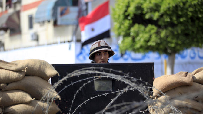 Egyptian soldiers stand guard outside the prison in Port Said, Egypt, Saturday, March 9, 2013. An Egyptian court on Saturday confirmed death sentences against 21 people for their role in a deadly 2012 soccer riot that killed more than 70 people in the city of Port Said. (AP Photo/Khalil Hamra)