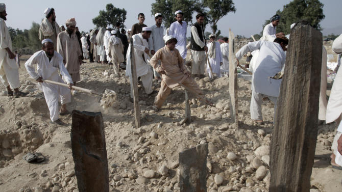 Afghan men prepare the graves of 14 civilians, killed a bomb explosion in Nangarhar province's Ghany Khel district, east of Kabul, Afghanistan, Thursday, Aug 8, 2013. Officials say a bomb planted in a graveyard in rural eastern Afghanistan has killed 14 members of the same family as they were marking the start of a major Muslim holiday with a visit to the tombs of relatives. (AP Photo/Rahmat Gul)