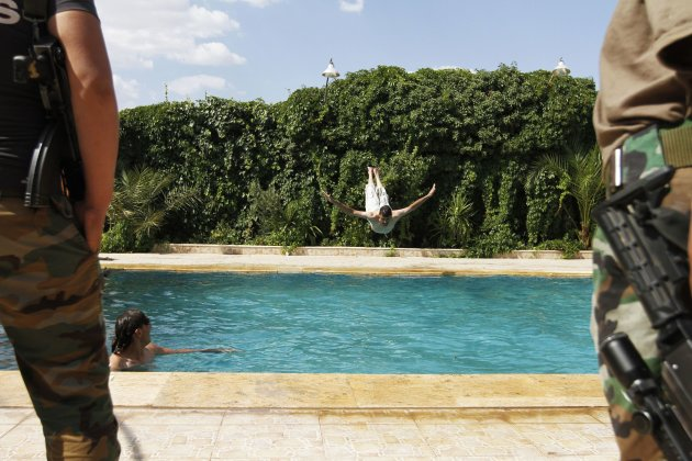 A member of the Free Syrian Army dives into a swimming pool in Aleppo