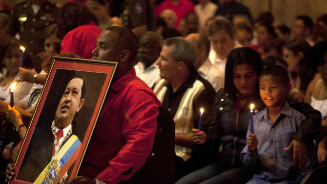 A man holds a framed image of Venezuela's President Hugo Chavez during a Mass to pray for the recovery of Chavez at the Cathedral, in Havana, Cuba, Saturday, Jan. 12, 2013. The 58-year-old president is fighting a severe respiratory infection a month after he underwent cancer surgery in Havana, his government says. (AP Photo/Ramon Espinosa)