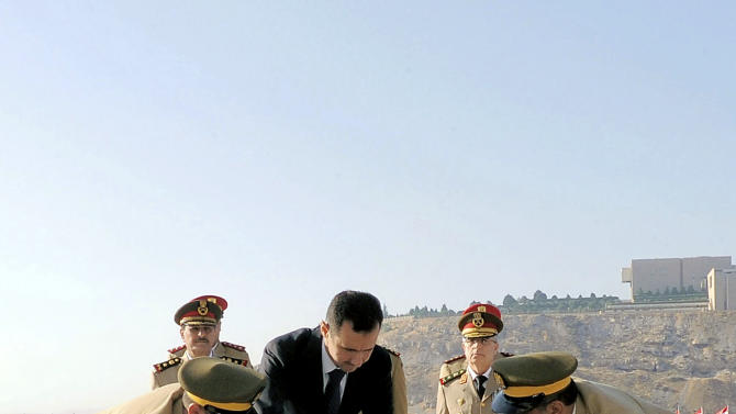 In this photo released by the Syrian official news agency SANA, Syrian President Bashar Assad lays a wreath at the tomb of the unknown soldier marking the anniversary of the 1973 Arab-Israeli war in Damascus, Syria, Saturday, October, 6, 2012. (AP Photo/SANA)