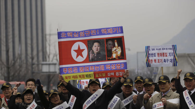 "A South Korean protester holds a poster with photos of North Korean leader Kim Jong Un and late leader Kim Jong Il with writing reading ""Nuclear test leaving their people starved? Overthrow  North Korea's dictatorship and strong punishment of North Korea's provocation,"" while others shout slogans during a rally demanding the Korean Peninsula's peaceful unification and denouncing North Korea's nuclear test near the U.S. Embassy in Seoul, South Korea, Monday, March 4, 2013. (AP Photo/Lee Jin-man)"