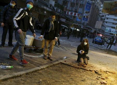 Protesters break a pavement for bricks to be thrown at riot police at Mongkok district in Hong Kong,