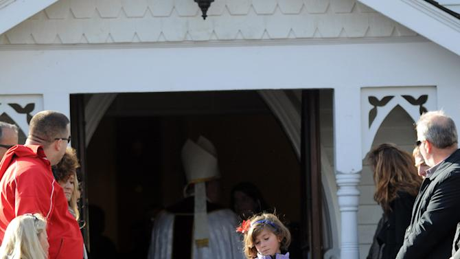 A young mourner exits St. Mary Of The Assumption Church in Katonah, N.Y. after the funeral for Anne Marie Murphy on Thursday, Dec. 20, 2012.  Murphy was killed when Adam Lanza, walked into Sandy Hook Elementary School in Newtown, Conn., Dec. 14, and opened fire, killing 26, including 20 children, before killing himself. (AP Photo/The Stamford Advocate, Lindsay Niegelberg) MANDATORY CREDIT