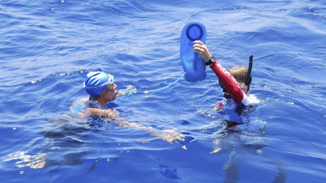 In this photo provided by Diana Nyad via the Florida Keys News Bureau, endurance swimmer Diana Nyad is hydrated by a crew member in the Florida Straits between Cuba and the Florida Keys Monday, Aug. 20, 2012. After being delayed by a weather squall line late Sunday night and early Monday morning, her team reported that Nyad was back on course in her effort to be the first swimmer to transit the Florida Straits from Cuba to the Keys without a shark cage. (AP Photo/Diana Nyad via the Florida Keys News Bureau, Christi Barli)
