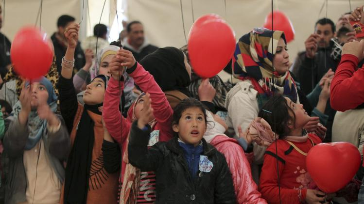 Young Syrian refugees release red balloons at Al Zaatari Syrian refugee camp in Mafraq
