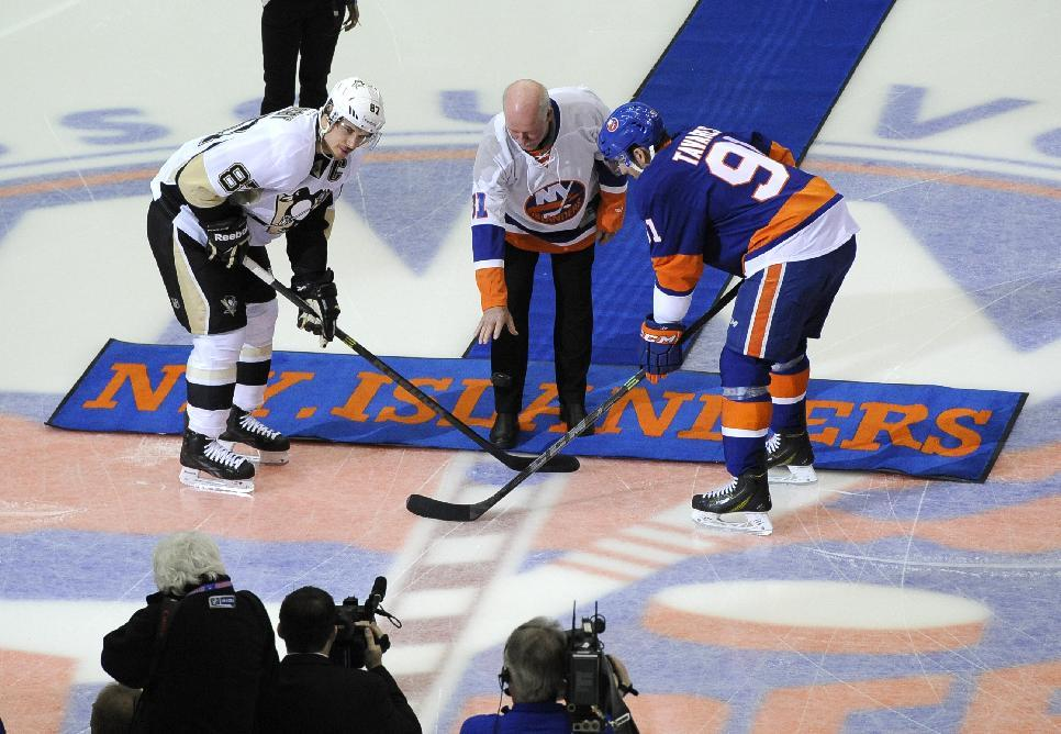 New York Islanders former goalie Billy Smith drops a ceremonial puck between Pittsburgh Penguins center Sidney Crosby (87) and New York Islanders center John Tavares (91) in the first period of an NHL hockey game at Nassau Coliseum on Saturday, Nov. 22, 2014, in Uniondale, N.Y