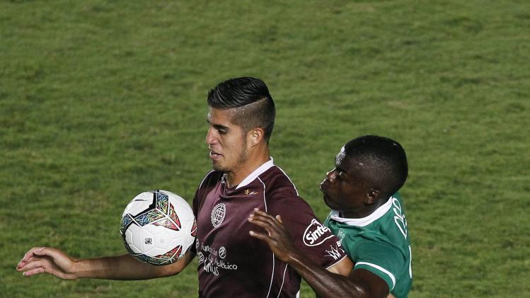 Mauricio Casierra of Colombia's Deportivo Cali and Oscar Benitez of Argentina's Lanus fight for the ball during their Copa Libertadores soccer match in Cali