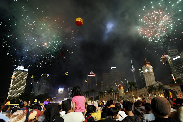 Malaysian people watch fireworks explode during the New Year celebrations at Independence Square in Kuala Lumpur, Malaysia, Sunday, Jan. 1, 2012. (AP Photo/Lai Seng Sin)