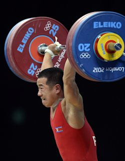 North Korea's Om Yun Chol competes during the weightlifting men's 56kg group B at the Excel Center in London during the 2012 London Olympic Games on July 29, 2012. AFP PHOTO / YURI CORTEZYURI CORTEZ/AFP/GettyImages