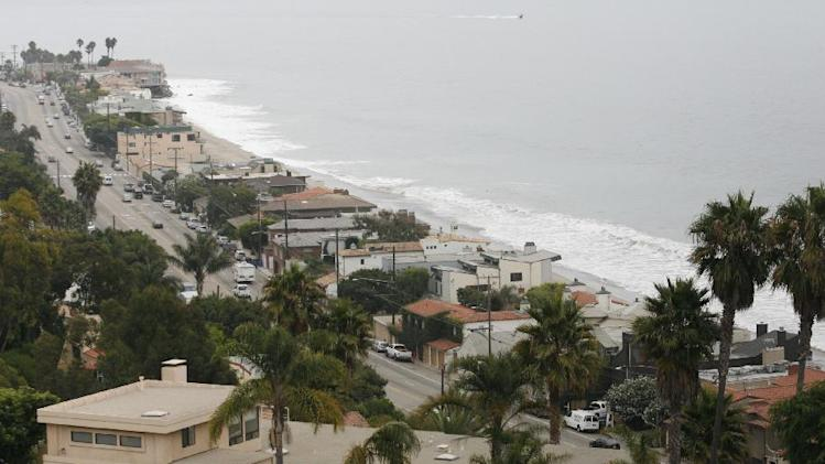 FILE - In this July 31, 2006 file photo, A portion of the Pacific Coast Highway runs through the affluent community of Malibu, Calif. It was a land of perfect waves and sparkling sand, in a place where there was a beach party every night and summer never ended. (AP Photo/Damian Dovarganes, File)