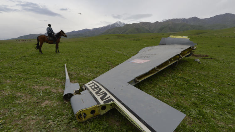 A U.S. Air Force KC-135 tanker aircraft wreckage is strewn across a field near the village of Chaldovar, about 100 miles (160 kms) west of the Kyrgyz capital Bishkek, Friday May 3, 2013. The emergencies ministry in Kyrgyzstan says a US military plane has crashed in the country. Kyrgyzstan hosts a US base that is used for troops transiting into and out of Afghanistan and for C-135 tanker planes that refuel warplanes in flight. (AP Photo/Vladimir Voronin)